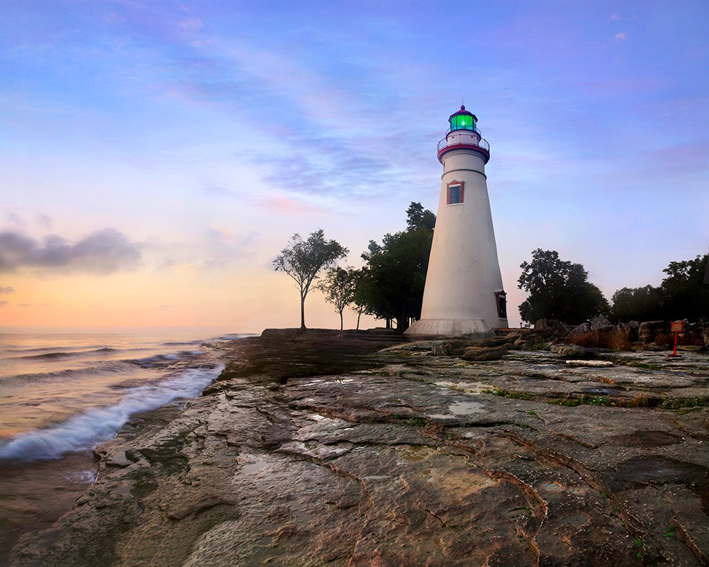 Marblehead Lighthouse and waves against rocks at sunrise