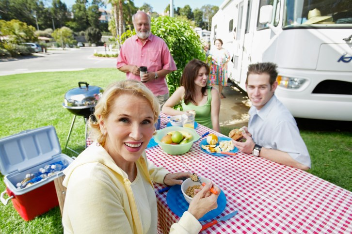 Senior Couple Sit Outdoors at a Table in Front of Their Motor Home, Having Breakfast With Their Teenage Grandchildren