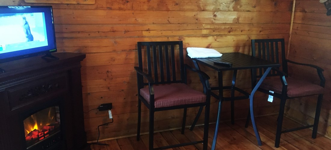 Inside Couple's Cabin Electric Fireplace & Bistro Set