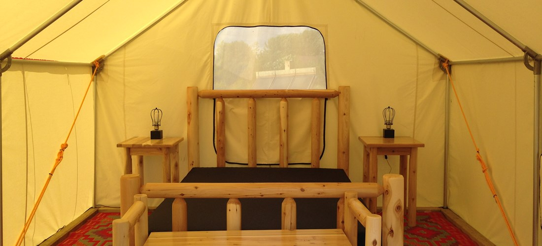 Rustic furniture is used for the Pioneer Tent.