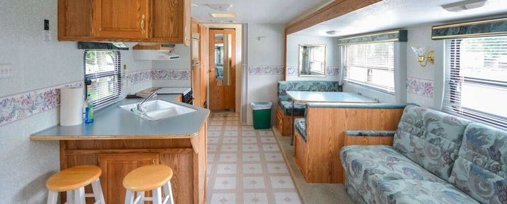 Inside a travel trailer: pull-out sofa in forefront, door to bathroom in back ground