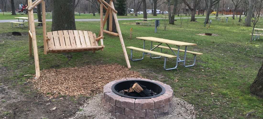 Premium Water & Electric RV site with rustic swing and enhanced fire ring.