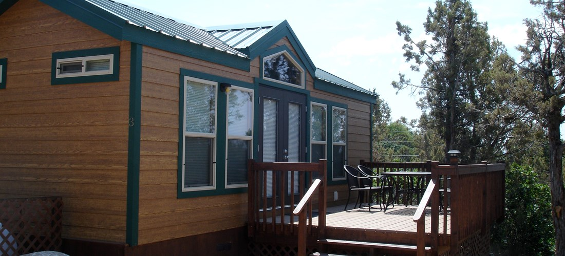 An outside view of one of our Deluxe Lodges that sleep up to 6 people. Includes a separate bedroom with a Queen bed, 1 Full Futon, 1 Set of Bunk Beds, Full Bath, Kitchenette, TV, A/C & Heat control, Large Deck with furniture, and a propane grill to the side of the Lodge.