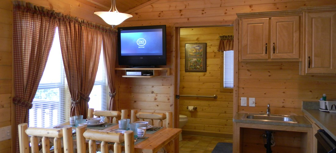 Inside view of the main area in our Handicap Lodge. Includes a dining table, TV, and a partial kitchen with kitchenware.