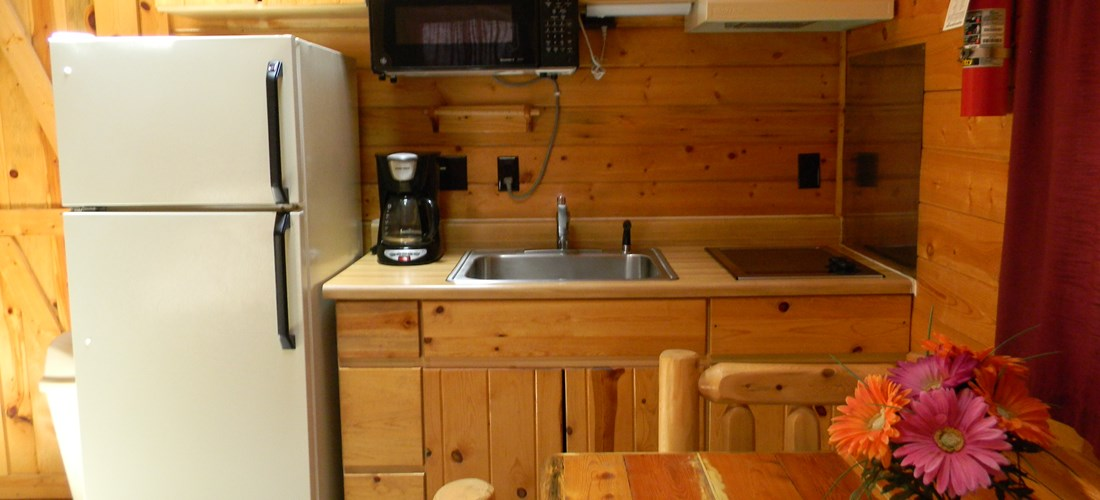 A look at the kitchen inside our Cottage. Includes kitchenware, a standard size refrigerator, microwave, small stove, coffee pot, and a cute dining area with a table and chairs.