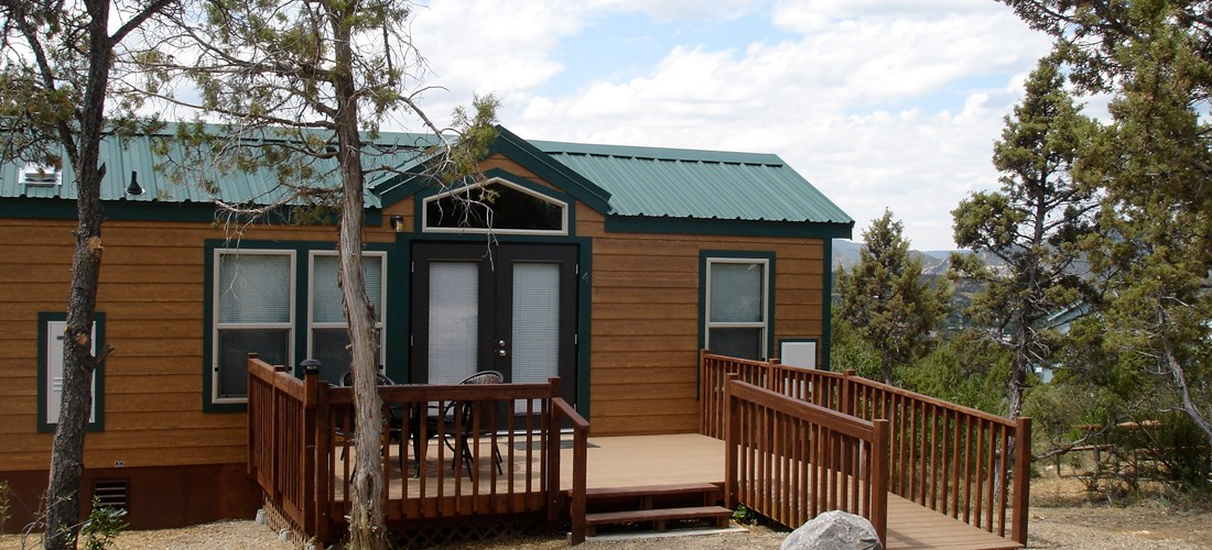 The outside view of our Handicap Lodge with a ramp for easy handicap access. Also includes a deck with furniture and a propane grill to the side of the Lodge.