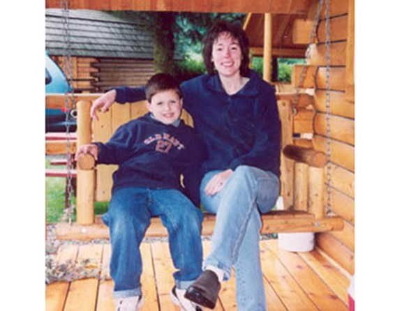 Mother & son laugh and swing on their Kamping Kabin porch.