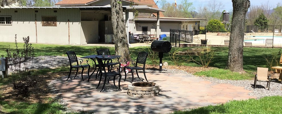 A site with extra amenities, patio, smoker grill, stacked fire ring, and shady.