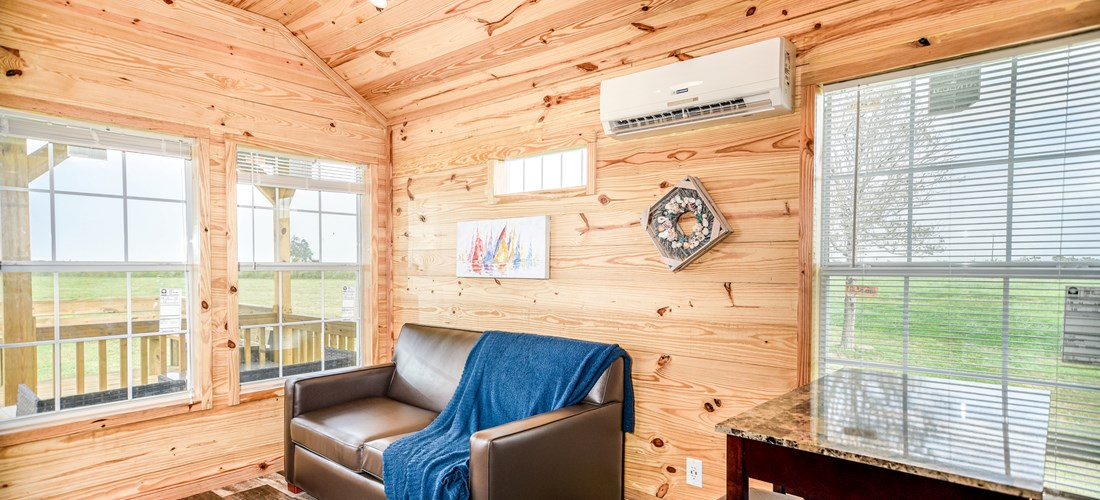 Our one bedroom cabin offers a kitchen area, dining table and a living space to relax on the sofa!