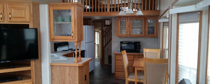 Fully stocked kitchen with view of loft in our deluxe cabin.