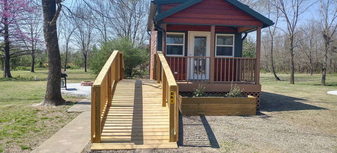Covered front porch and ramp are just a few of the amenities with our deluxe cabin!