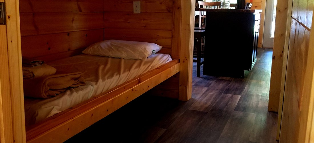 So many sleeping options in your cottage! These bunkbeds are oversized and include a reading lamp and plug in each. A door on either end provides privacy.