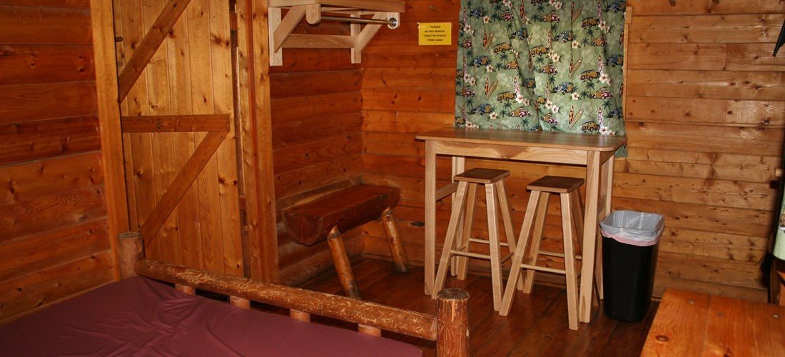 Inside a Two Room Cabin, front room with a full size bed and small table.