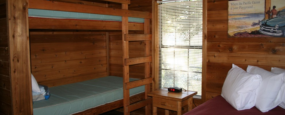 The bedroom has a full size bed and a set of bunks.