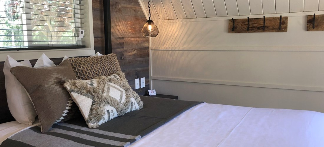 Queen bed with full linens in Patio Glamping Cabin
