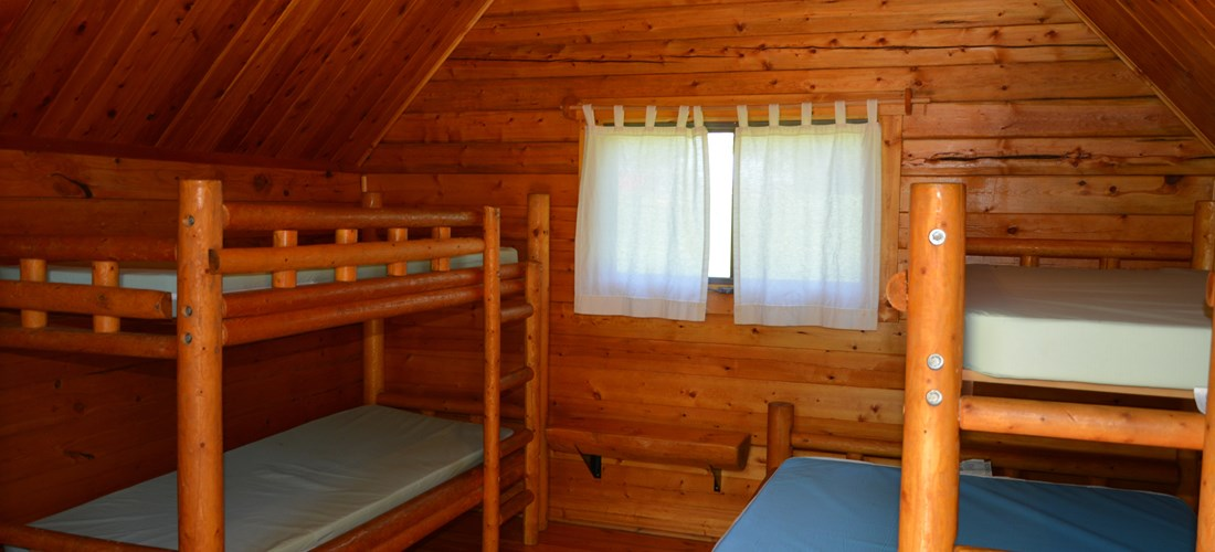 Inside 1 room camping cabin that sleeps 5.