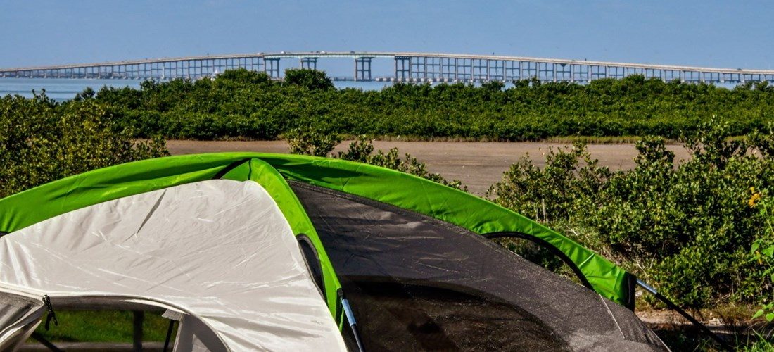 Look to the bridge from your tent site and watch the parasailers
