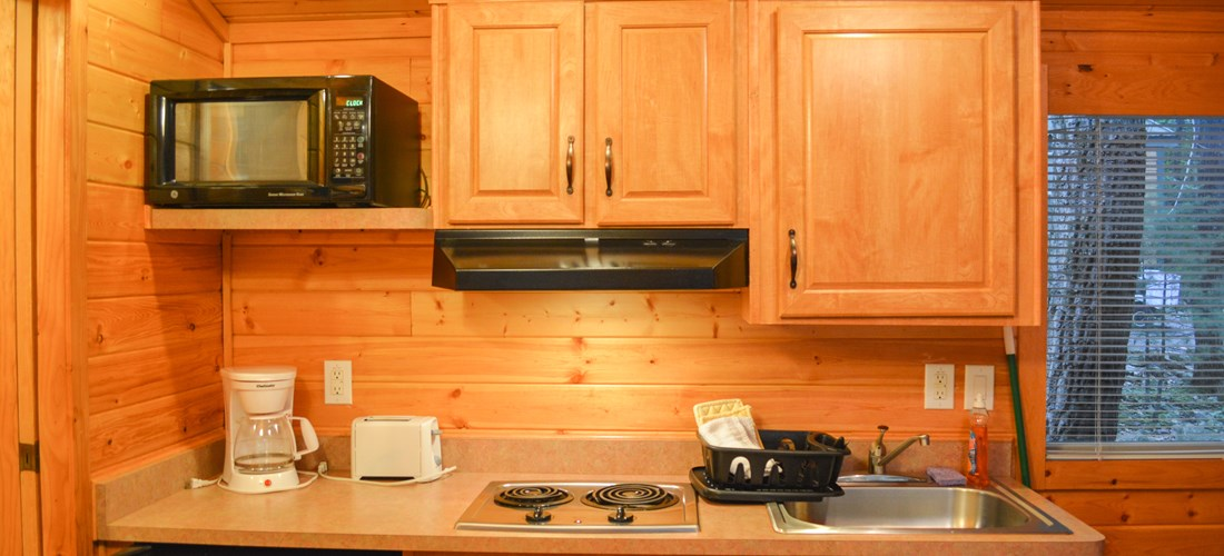 The Deluxe Cabin comes with a mini fridge, stove, toaster, microwave, and kitchenware.